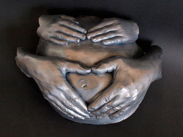 escultura embarazada y manos de familia
